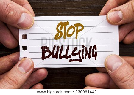 Handwritten text sign showing Stop Bullying. Business concept for Awareness Problem About Violence Abuse Bully Problem written Sticky Note Paper Holding Hand with Finger. poster