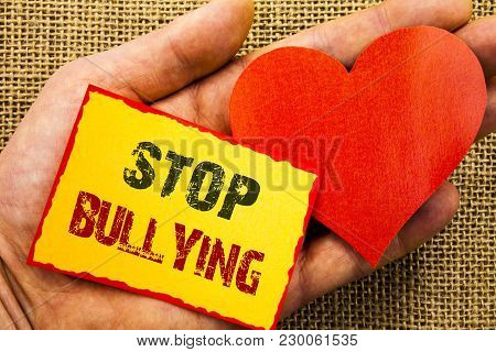 Handwriting text showing Stop Bullying. Business concept for Awareness Problem About Violence Abuse Bully Problem written Sticky Note Paper With Heart Holding Hand with Finger. poster