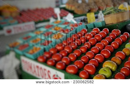 A colorful farmers market tomato booth with background bokeh blur.