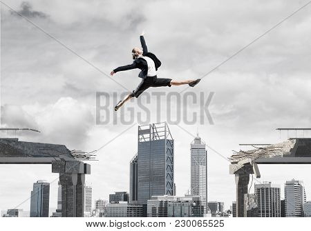 Business Woman Jumping Over Gap In Concrete Bridge As Symbol Of Overcoming Challenges. Dark Sky And