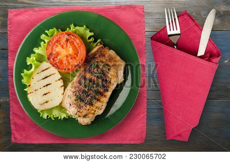 Pork Grilled With Potatoes And Tomato On A Wooden Background. Grilled Pork On A Plate Top View