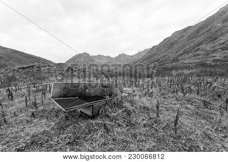 A Large Industrial Sink In A Valley Between Two Mountains In Alaska.