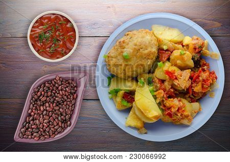 Cutlets With Potatoes And Stewed Tomatoes. Cutlet On A Plate On A Wooden Background