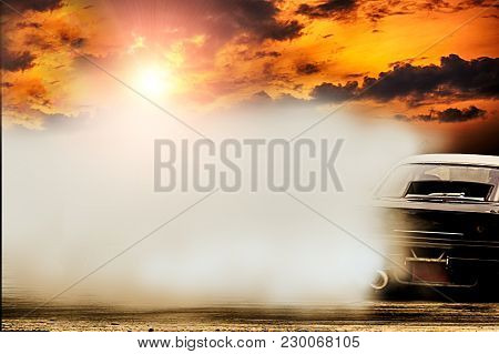 Abstract Blurred Drift Car With Smoke From Burned Tire At Sunset.