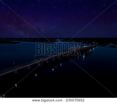 Aerial view of bridge at night with the milky way in the sky.