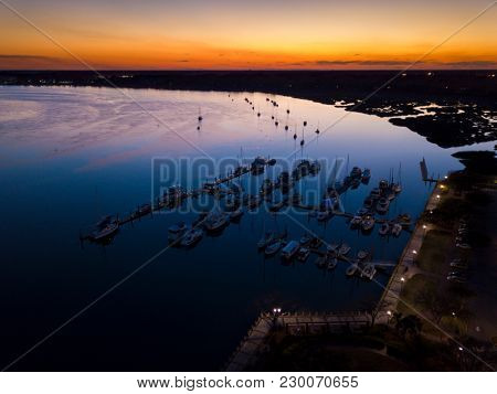 Aerial view of marina and sailboats at twilight.