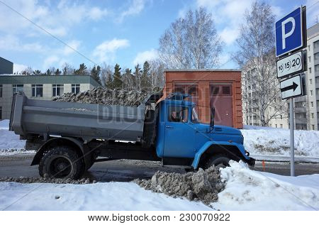 Russia, Koltsovo - March 07, 2018: Snow clearing loaded dump truck on street full of dirty snow from road in science city in Siberia near Novosibirsk. Russian car ZIL