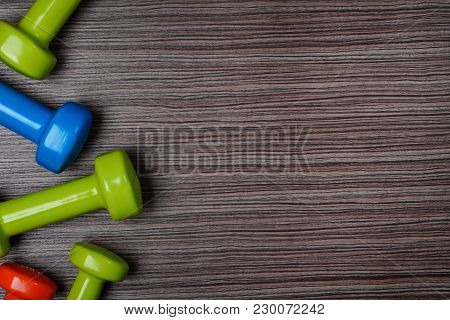 Many Blue Green And One Orange In The Middle Dumbbells On A Background ,concept Preparing To Fitness