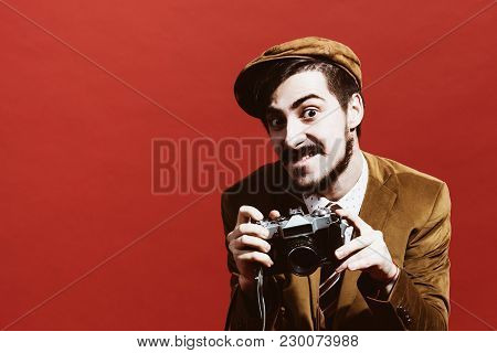 Very Positive Photographer Posing In Studio With Film Camera