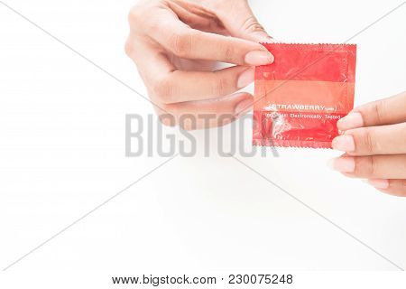 Woman's Hands Holding Condom On White Background With Copy Space, Safe Sex Concept