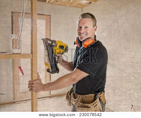 Attractive And Confident Constructor Carpenter Or Builder Man Working Wood With Electric Drill At In