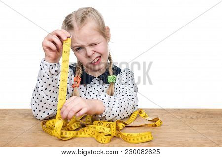 Little Beautiful Girl Sitting At The Table Doing A Measuring With A Tape Measure Isolated On A White