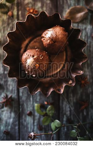 Cupcakes On A Dark Wooden Background With Rose Branches