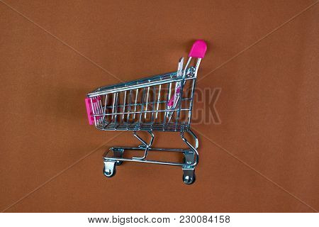 Shopping Cart Or Supermarket Trolley On Brown Background, Business Finance Shopping Concept.
