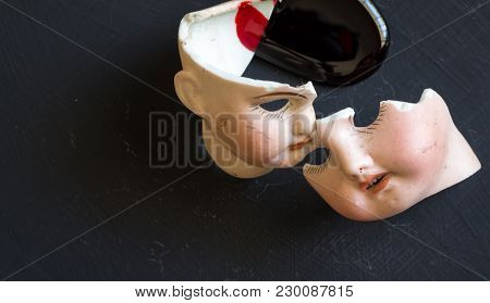 Broken Doll Faces And Blood Isolated On Grunge Black Background With Blood Spatter. Conceptual Image