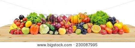 Vegetables and fruits on wooden table boards isolated on white background.