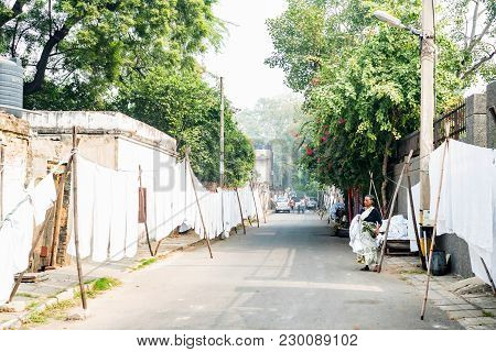 Agra, India - November 8, 2017: Street Laundry With White Bed Sheets Hanging On Ropes In India. Agra