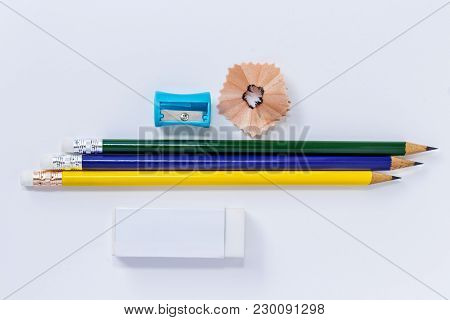 Pencil-sharpener, Eraser, And Many Pencils Isolated On White Paper Background. With Copy Space For Y