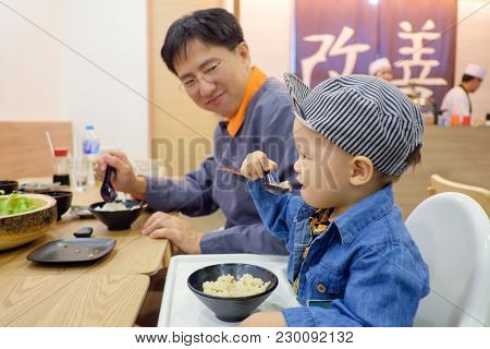 Cute Asian 18 Months Toddler Baby Boy Child Eating Food With Fork & Spoon By Himself At Japanese Res