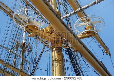 Steel Masts Of A Sailing Ship With The Lowered Sails With Blue Sky On The Background.