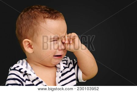 Portrait Of Baby Boy Crying against a black background