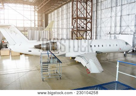 Passenger Aircraft, Side View - On Maintenance Of Engine On Tail And Fuselage Repair In Airport Hang