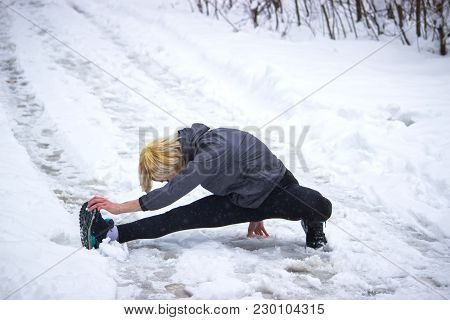 The Girl Shows Exercise A Twine On The Street In The Winter