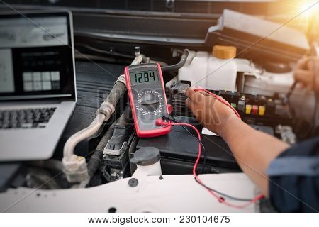 Auto Mechanic Using Digital Multimeter To Check The Fuse In A Car,check Voltage Level Car Battery.