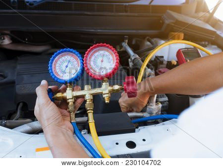 Auto Mechanic Using Gauge Air Conditioning Pressure In Auto Vehicle.