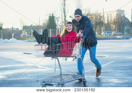 Two Happy Hipsters Having Fun With Shopping Cart Outdoors