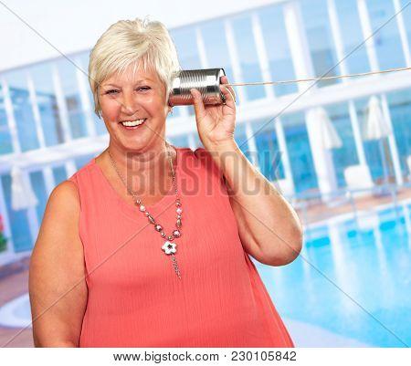 Senior Woman Hearing On Metal Tin Can Phone, Outdoors