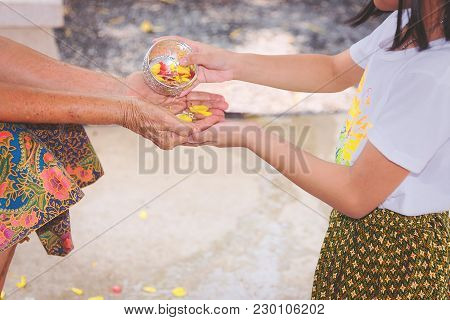 Young Little Woman Pouring Water On Hands Of Senior For Blessing On Songkran Day In Thailand,thai Ne