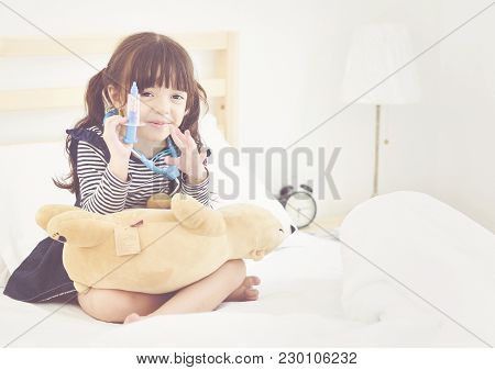 Cute Little Girl Played In Doctors On The Bed.family And Relaxing Concept.