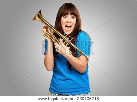 surprised woman holding trumpet isolated on gray background