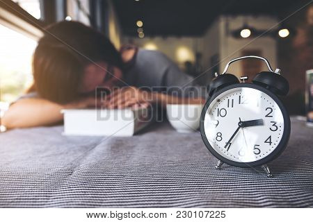 An Asian Woman Taking A Nap While Reading A Book With Black Alarm Clock On The Table
