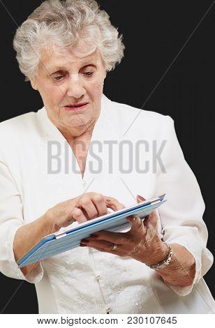 Senior woman using ipad isolated on black background
