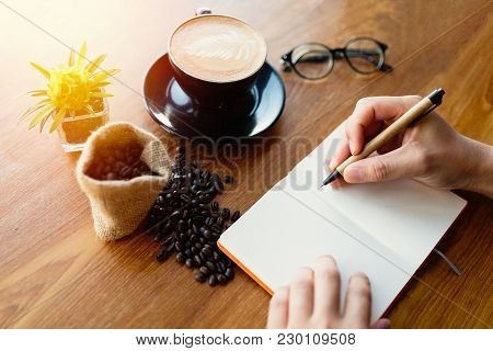 Man Writing Notebook With Coffee At Coffee Shop.