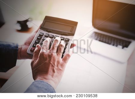 Man Using Calculator,finance And Economy Concept Through A Laptop.