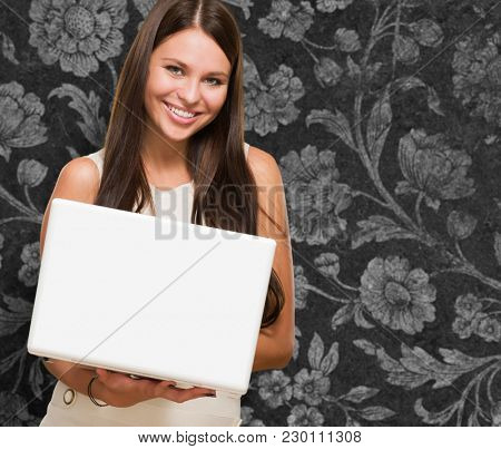 Beautiful Young Woman Holding A Computer against a vintage background