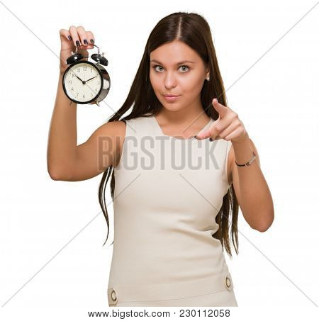 Woman Holding Alarm Clock and pointing against a white background