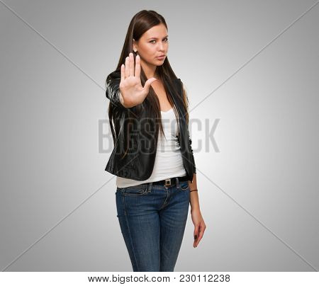 Young Woman Showing Stop Hand Gesture against a grey background