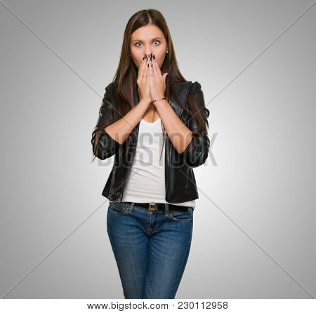 Surprised Woman covering her mouth against a grey background