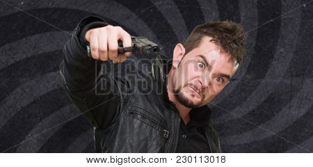 furious man pointing with a gun against a spiral background