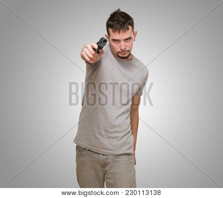 mad man pointing with gun against a grey background