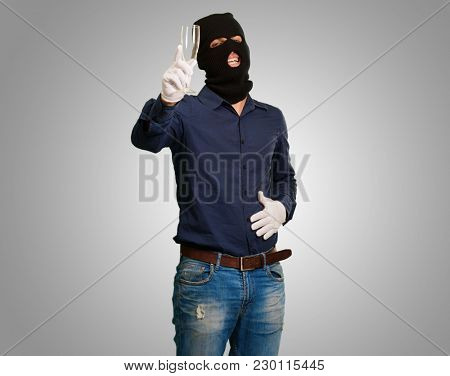 Burglar Man Holding Champagne Glass against a grey background