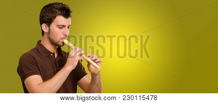 Portrait Of A Young Man Playing Flute On Coloured Background