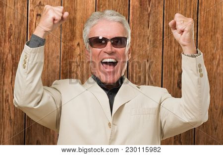 Mature Man With Doing A Success Gesture against a wooden background