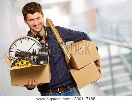 Young Man Holding Cardboxes Gesturing, Indoor