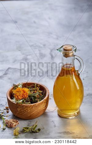 Spa Still Life With Flowers In Wooden Bowl And Two Oil Jars On Light Textured Background, Top View,