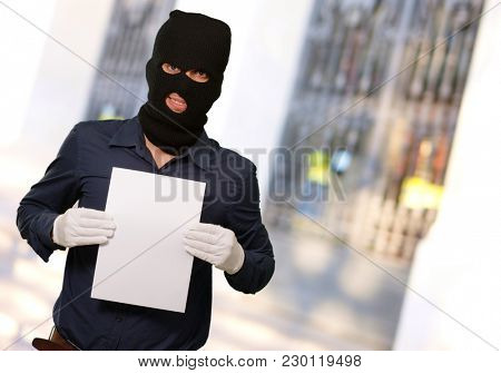 Man wearing a robber mask showing a blank paper, outdoor